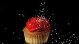 Sprinkles falling onto red iced cupcake
