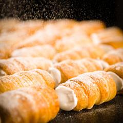 Powder sugar falling on to cream horns
