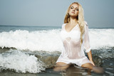 beautiful wet blond woman in water on a beach