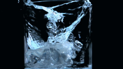 Two ice cubes falling into glass on black background