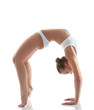 Sporty girl doing gymnastic bridge in studio