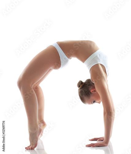 Sporty girl doing gymnastic bridge in studio