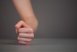 Female fist hits on the table.