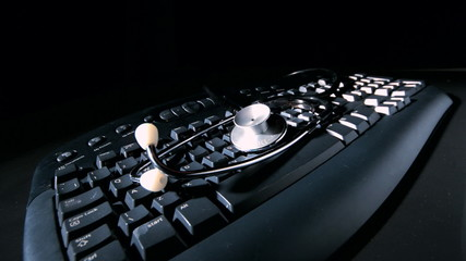 Stethoscope falling onto computer keyboard and vibrating