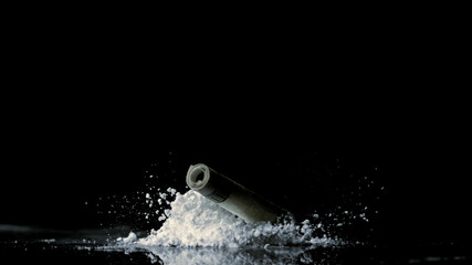 Rolled up dollar note falling on pile of white drug on black background