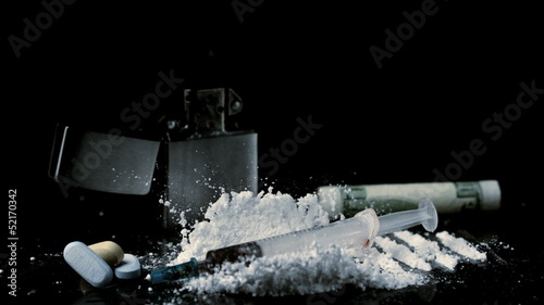 Syringe falling on pile of white drug with syringe rolled up dollar and tablets