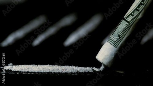 Someone snorting a line of cocaine with other lines in background