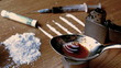 Drug cooking on a spoon surrounded by pile lines and syringe on wooden table