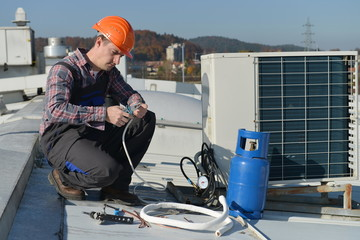 Air Conditioning Repair, young repairman on the roof fixing AC