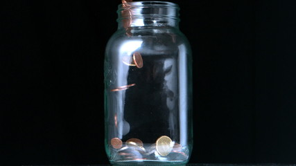 Coins pouring into glass jar