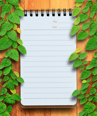 Blank planning notebook on wood background with ivy fixing tree.