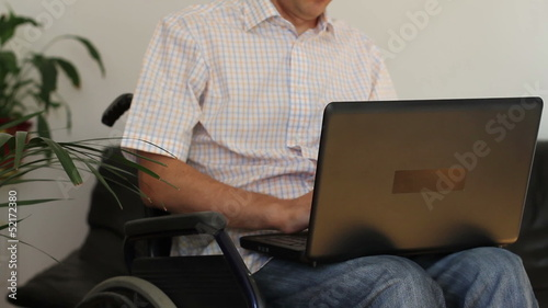 Businessman in wheelchair working on laptop computer