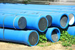 Stacked blue PVC pipe on construction site