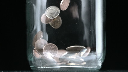 Many coins pouring into glass jar close up