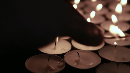Hand lighting tea light candles with match