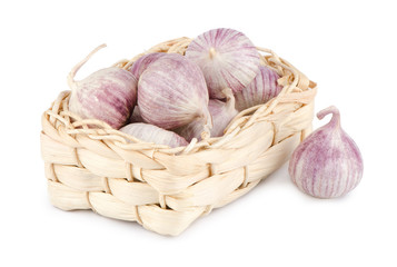 Several garlic in a wicker basket isolated on white