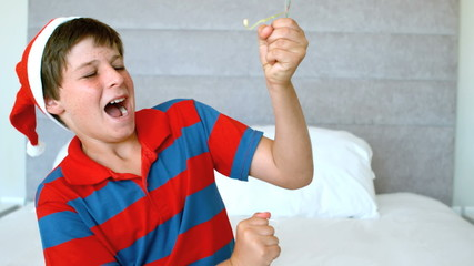 Happy boy using party popper in the bedroom