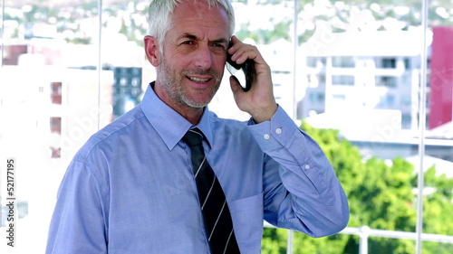 Businessman answering his phone and looking impressed