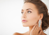 woman wearing shiny diamond earrings - 52177703