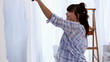 Attractive woman jumping to paint her wall in blue