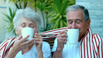 Retired couple enjoying coffee outside in slow motion