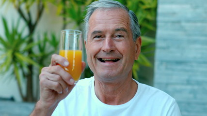 Retired man toasting with orange juice outside in slow motion