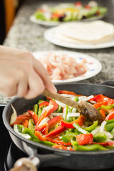 Closeup of female cooking vegetables and chicken in a pan