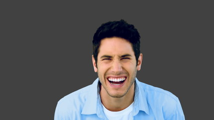 Man laughing at the camera on grey background