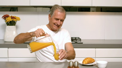 Retired man pouring orange juice for breakfast