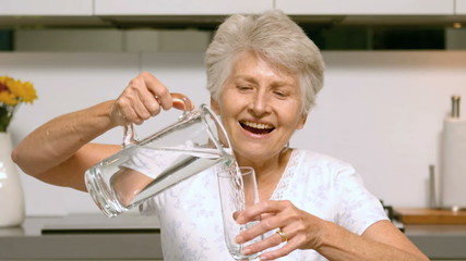 Retired woman pouring glass of water