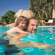 Child and father in swimming pool