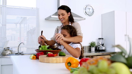 Mother and daughter tossing salad together