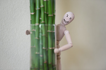 Wooden man standing at home and looking out of the tree. People