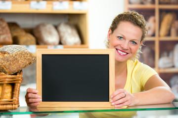 verkäuferin in bäckerei mit hinweisschild