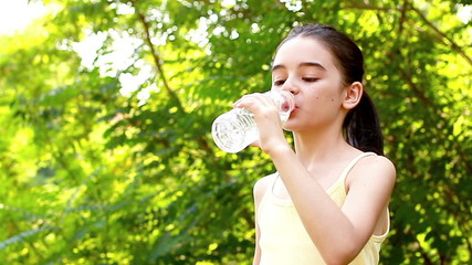 Teenage girl drinking water out of a plastic bottle