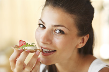 Young happy woman eating sandwich