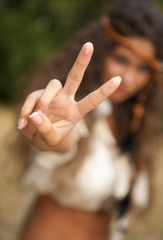 Beautiful hippie girl in the park making the sign of peace