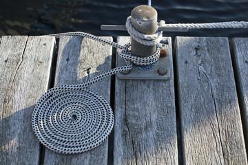 Aufgerollte Seil auf einem Bootssteg