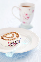 Slice of roll cake with tea and dried flower petals