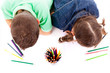 Top view of two children drawing with colorful crayons, isolated