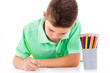 Little boy drawing with colorful crayons, isolated over white