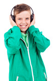 Portrait of happy smiling young boy listening to music on headph