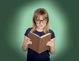 Beautiful little girl with glasses and a book reading