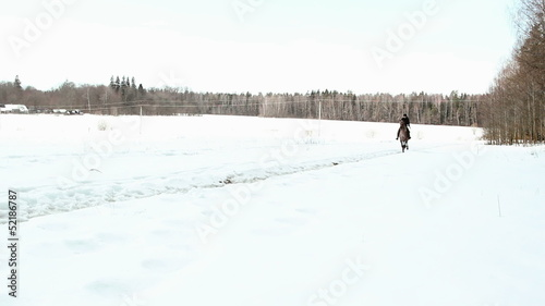 female cowboy rides a horse at a gallop in winter