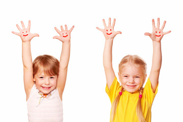 Two little girls raising their hands up. Young students