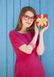 redhead girl in glasses with gift near wood background