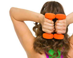 Woman athlete making exercise with dumbbells . rear view