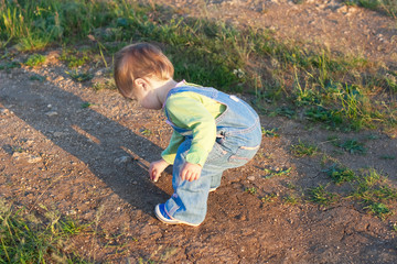 little child in the jeans coverall pick up stones