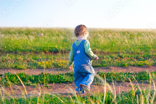 child  in the jeans coverall walk on the dirt road