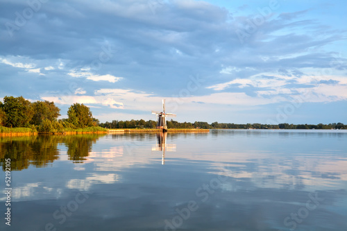 charming windmill by lake before sunset